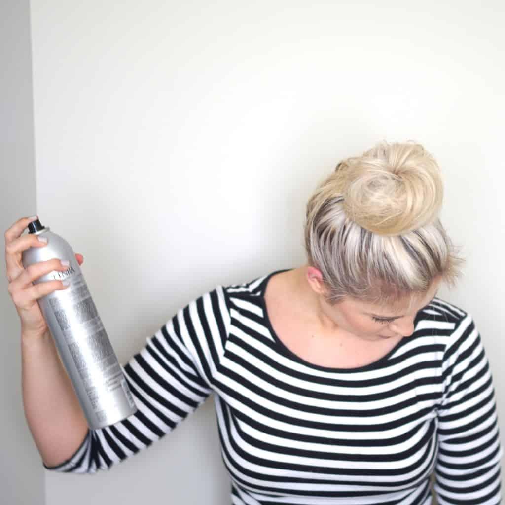spraying hair after a bun